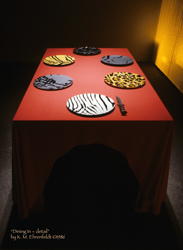 table settign from head of table showing 6 animal skin patterned plates, and a hunting knife